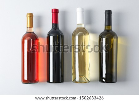 Bottles with different wine on grey background, top view #1502633426