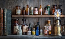 Bottles with drugs from old medical, chemical and pharmaceutical glass. Chemistry and pharmacy history concept background. Retro style. Chemical substances.