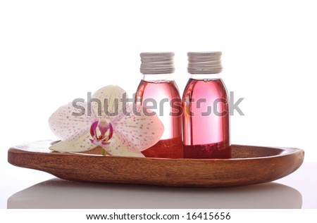 bottles with essential oils  and orchid in bowl isolated on white background