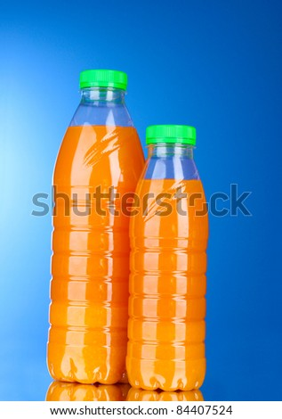 Bottles with juice on blue background