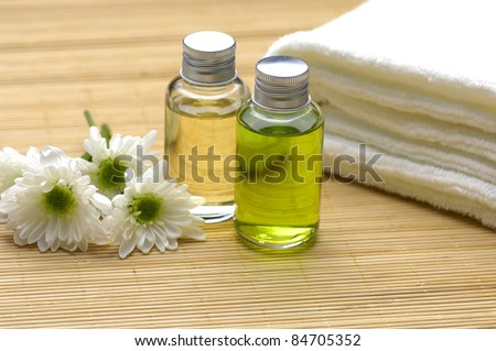 bottles with massage oils and towel with flower on bamboo stick straw mat