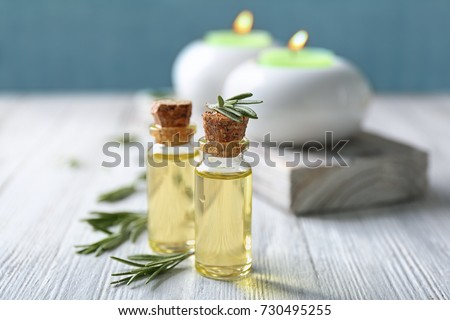 Bottles with rosemary oil and herb on wooden table #730495255