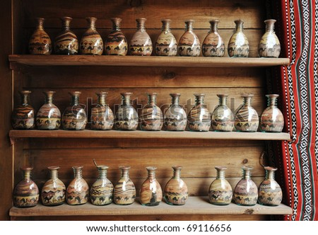 Bottles with sand shapes on shelves, simple pieces handmade by little children in huge numbers, local souvenirs in Jordan (no copyright)