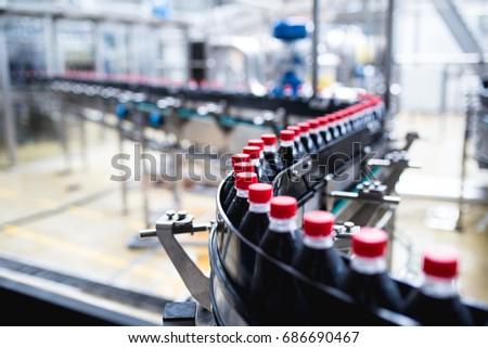 Bottling factory - Black juice bottling line for processing and bottling juice into bottles. Selective focus.  #686690467