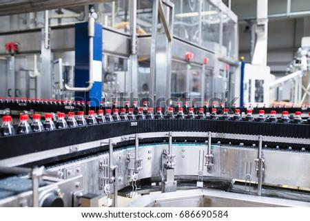 Bottling factory - Black juice bottling line for processing and bottling juice into bottles. Selective focus.  #686690584
