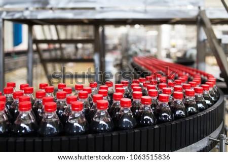 Bottling factory - Black juice or soft drink bottling line for processing and bottling juice into bottles. Selective focus.  #1063515836