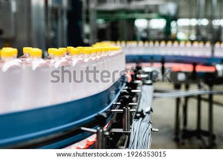 Bottling factory - Juice bottling line for processing and bottling lemon juice into bottles. Selective focus.