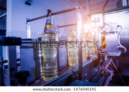 Bottling line of sunflower oil in bottles. Vegetable oil production plant. High technology. Industrial background stock photo