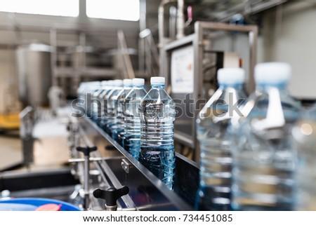 Bottling plant - Water bottling line for processing and bottling carbonated water into blue bottles. Selective focus.  #734451085