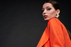 Bottom angle, portrait of attractive glamorous stylish woman with evening make-up, posing in a trendy orange suit in the studio, against a dark background. Copy space.
