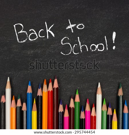 Bottom border of colorful pencil crayons against a blackboard with Back to School writing in chalk