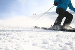 bottom half of skiier coming down mountain spraying snow
