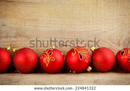 Bottom line of red baubles christmas ornaments on wooden surface planks