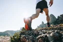 Bottom of running sneaker shoe sole on hard rocky terrain on mountain path during ultra trail marathon race. Strong fit healthy athletic man, trained legs during workout outdoors