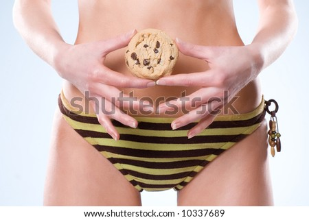 Bottom part of woman wearing a swimsuit and holding a cookie in front of her stomach