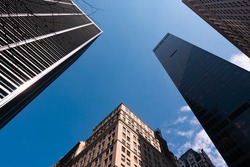 Bottom street view on skyscrapers of New York City with blue sky background. Downtown area, wide angle shot, copy space, place for text
