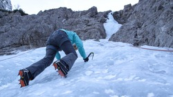 BOTTOM UP, CLOSE UP: Caucasian woman ice climbing in the Julian Alps stops and looks at her crampons Fearless female tourist goes ice climbing up the gorgeous icy stream running down the rocky cliff