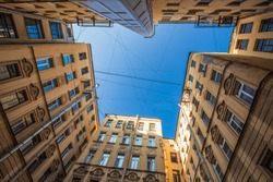 Bottom-up view from a non-rectangular courtyard surrounded by multi-storey buildings. The blue sky above the courtyard is lined with intersecting wires. European city. No people