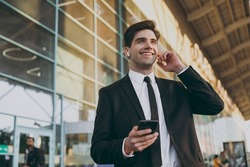 Bottom view happy traveler businessman man in black dinner suit earphones stand outside at international airport terminal talk on mobile phone book taxi order hotel Air flight business trip concept.