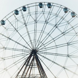 Bottom view of a brown metallic ferris wheel against a clear blue sky in an amusement park