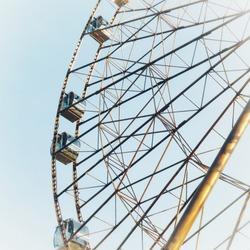 Bottom view of a brown metallic ferris wheel against a clear blue sky in an amusement park