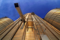 Bottom view of a modern metal silo at sunset