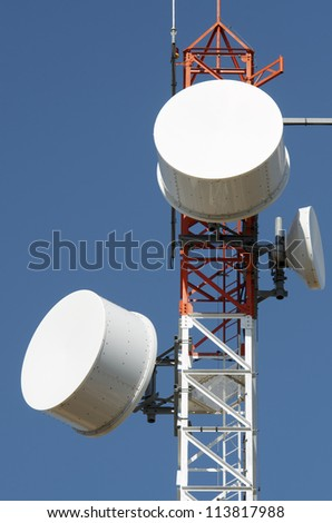 bottom view of  a telecommunications tower with a clear blue sky.