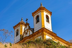 Bottom view of antique and historic church in 18th century colonial architecture on top of the hill in the city of Ouro Preto in Minas Gerais, Brazil with the mountains behind