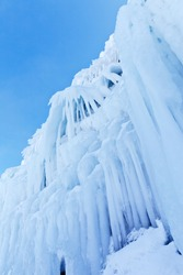 Bottom view of beautiful icy coastal cliffs with blue long icicles on a winter sunny day. Frozen Baikal Lake, Olkhon Island. Natural cold background. Winter unusual landscape