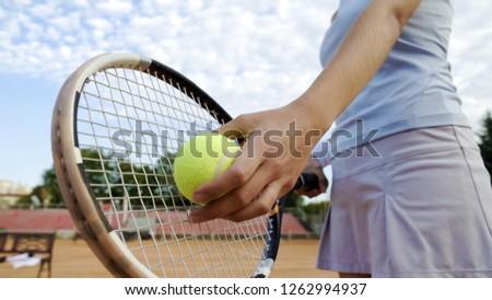 Bottom view of beautiful woman serving tennis ball, professional sport, hobby