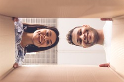 Bottom view of beautiful young couple looking through the cardboard box and smiling