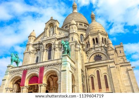 Bottom view of facade of Sacred Heart of Paris church in France. Basilique du Sacre-Coeur de Montmartre, the historic district of Paris Capital. Popular tourist landmark in a Capital of France.