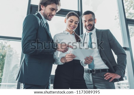 bottom view of happy business people using tablet together at modern office #1173089395