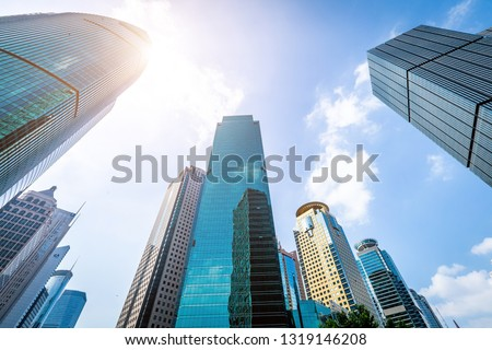 Bottom view of modern skyscrapers in business district against blue sky #1319146208