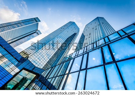 Photo of  Bottom view of modern skyscrapers in business district against blue sky