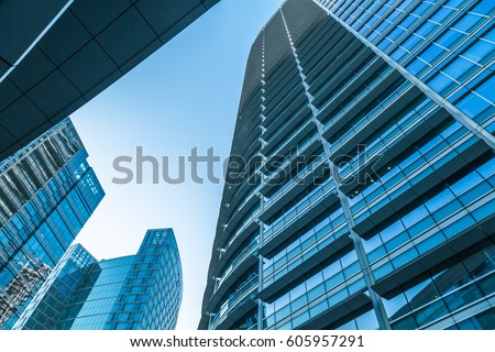 Bottom view of modern skyscrapers in business district against blue sky #605957291