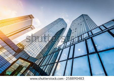 Bottom view of modern skyscrapers in business district at sunset with lens flare filter effect