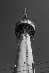 Bottom view of monumental concrete telecommunication tower with beacon, under clear sky in sunlight. Vertical architecture, copy space for text