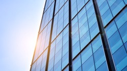 Bottom view of office building window close up with sunrise, reflection and perspective. Modern architecture with sun ray. Glass facade on a bright sunny day with sunbeams on the blue sky.