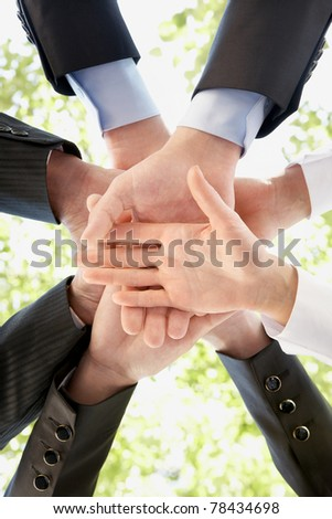 Bottom view of people hands holding together on background of green foliage