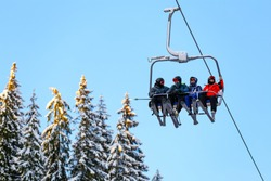 Bottom view of ski family on chair lift in vacation in the mountains. Father, mother and two children with skis and ski gear.