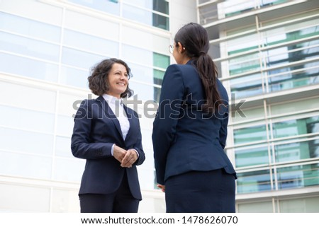 Bottom view of smiling colleagues standing on street. Cheerful young confident employees wearing formal suits looking at each other. Business confidence concept