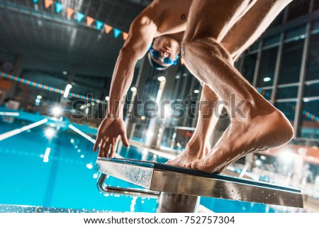 bottom view of swimmer jumping into competition swimming pool
