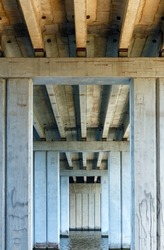 Bottom view of symmetrical concrete truss structures, concrete beams and pillars of the bridge that crosses the river and supports the six-lane expressway. Vertical image, copy space.