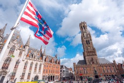 Bottom view of the Belfort Tower and the flagpole with the flag of Bruges from the side of the square in Bruges against the backdrop of a beautiful sky with white clouds, Belgium