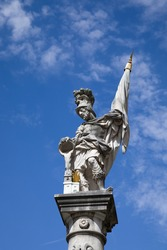 Bottom view of the St. Florian statue against the blue sky with clouds on Old Market Square (Alter Markt) in the Historic Centre of the Salzburg, Austria. St. Florian is the patron of firefighters.