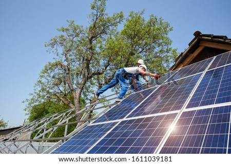 Bottom view of two technicians on metal platform installing solar photo voltaic panels on bright sunny day. Stand-alone solar panel system installation, efficiency and professionalism concept.