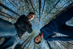 Bottom view of woman and man in the forest on the background of tops of tall trees and blue sky. Young couple in casual wear walks in the woods. Wide angle shot of hikers in nature. Summer adventures