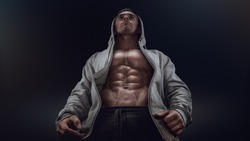 Bottom view of young strong bodybuilder showing off his physique against black background. Confident young fitness man with strong hands, abs and abdominal muscles. Dramatic light.