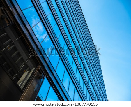 Bottom view on Glass wall in modern architecture skyscrapers in business center district against blue sky. Success element #1389770135